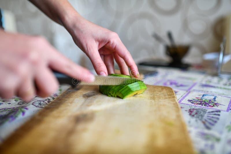 Flickasnittavokado på brädet Flickan klipper den gröna mogna avokadot med kniven Frukt klipps på träskärbräda Slapp fokus arkivbilder