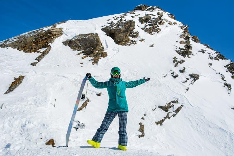 Flickasnowboarder på bakgrunden av höga snö-korkade fjällängar i s royaltyfri fotografi