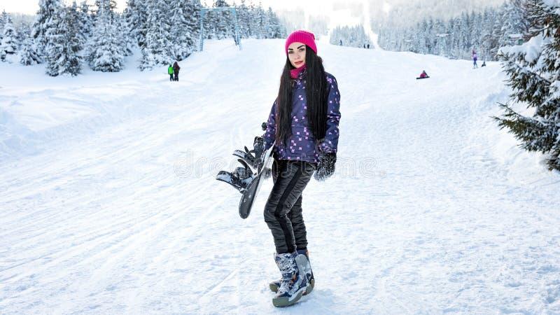 Flickasnowboarderställningar bara på en skidalutning i vinter royaltyfri foto