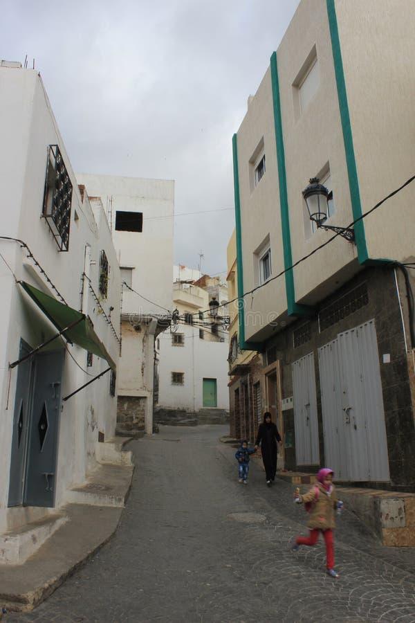 Flickaspring i gatan i Tetouan, stad i Marocko/Nordafrika, byggnad vid solnedgång royaltyfri bild