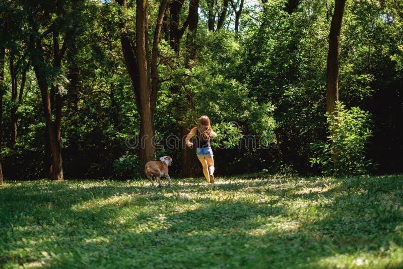 Flickaspring med hennes hund i parkera fotografering för bildbyråer