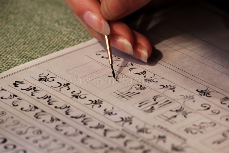 Flickastudenten lär att dra monogram för att dra dem på spikar, när han skapar en manikyr med färgschellack akryl svart p royaltyfri bild
