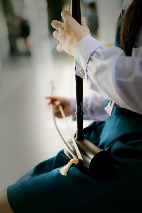 Flickastudenten spelar det thai musikinstrumentet, tredubbel lurendrejeri, violonsopran arkivbilder