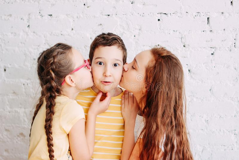 Flickasystrar som kysser pojkebrodern med två sidor som isoleras på vit tegelstenbakgrund royaltyfri foto