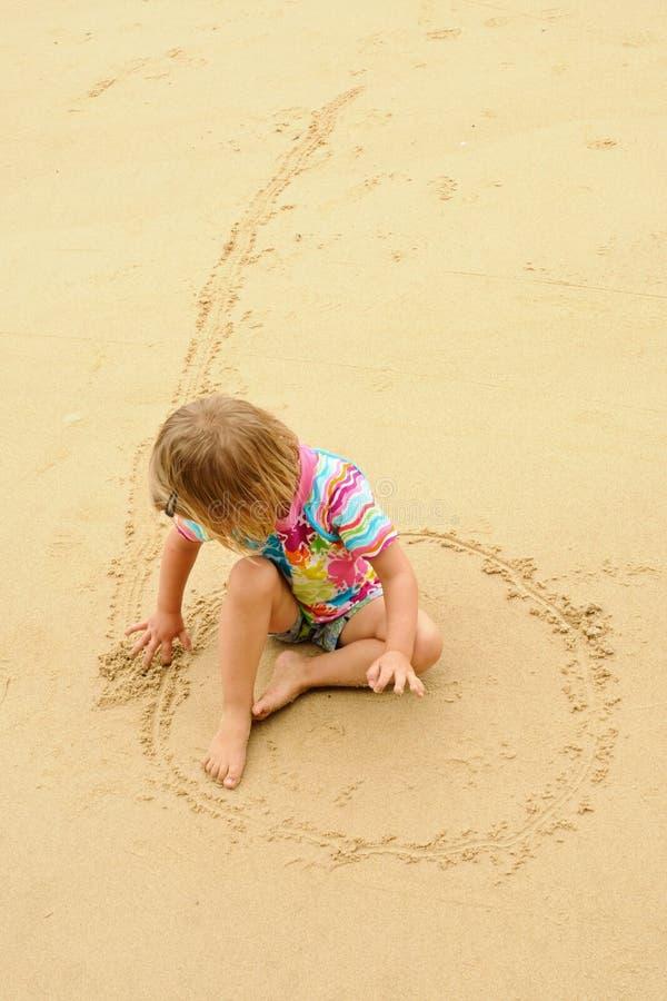 Flickateckning på sanden royaltyfri bild