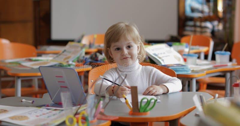 Flickateckning p? tabellen i klassrum Utbildning Barn som sitter p? ett skrivbord royaltyfri fotografi