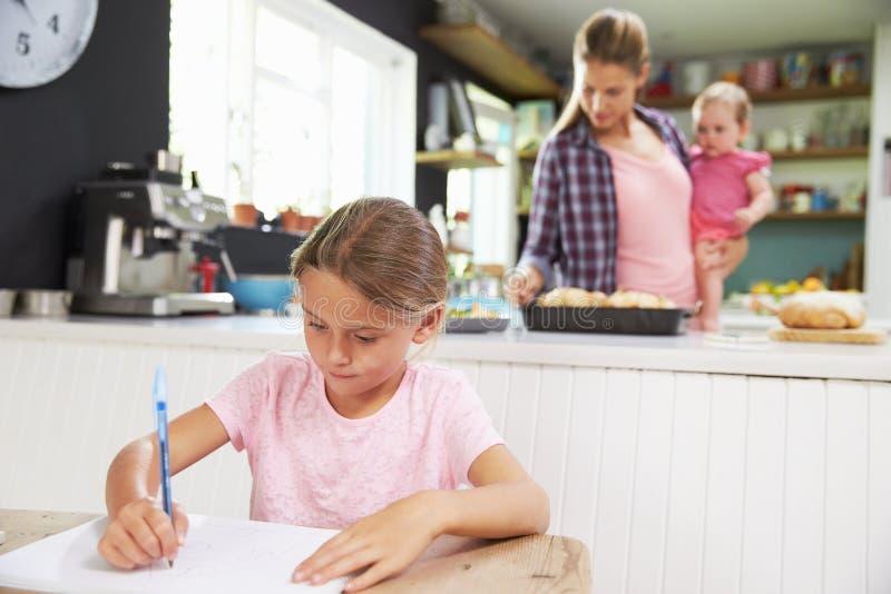 Flickateckningsbilden som moder förbereder mål i kök royaltyfri fotografi