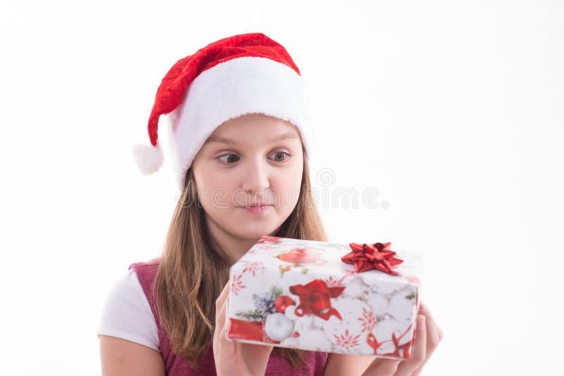 Flickatonåring med en gåva i en jultomtenhatt arkivbilder