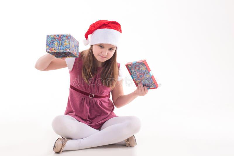 Flickatonåring med en gåva i en jultomtenhatt royaltyfria bilder