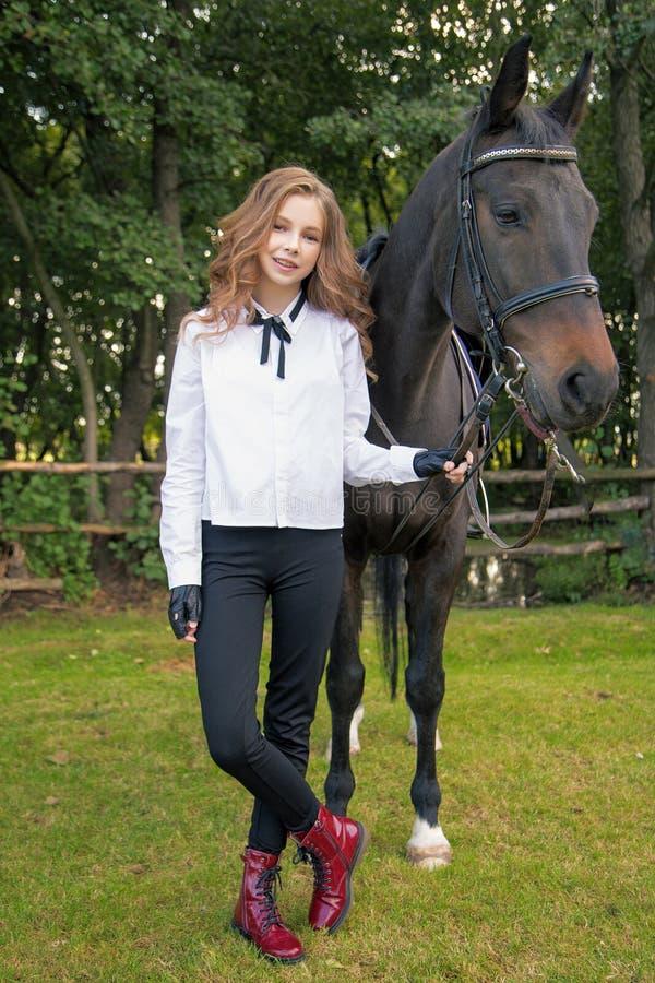 Flickatonåring med en häst arkivfoto