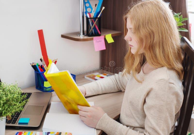 Flickatonåring som gör läxa arkivbild