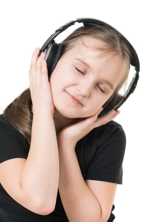 Flickatonåring som lyssnar till musik med stor hörlurar och pensively ser upp arkivbilder