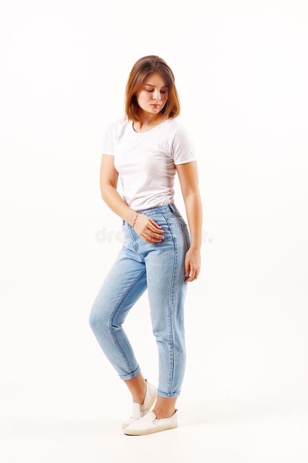 Flickatonåringen i den vit t-skjortan och jeans poserar arkivfoton