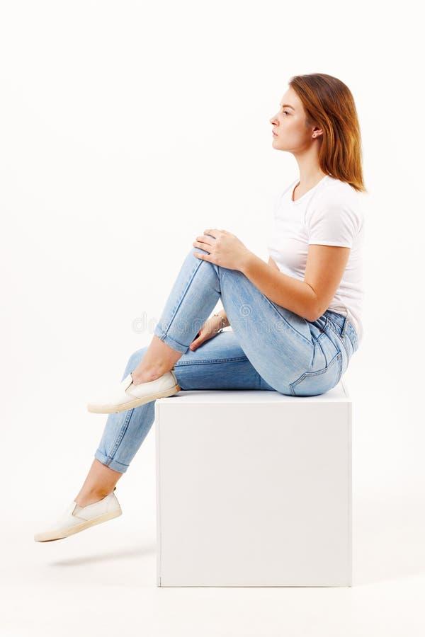 Flickatonåringen i jeans sitter på kuben i den vita studion royaltyfria foton