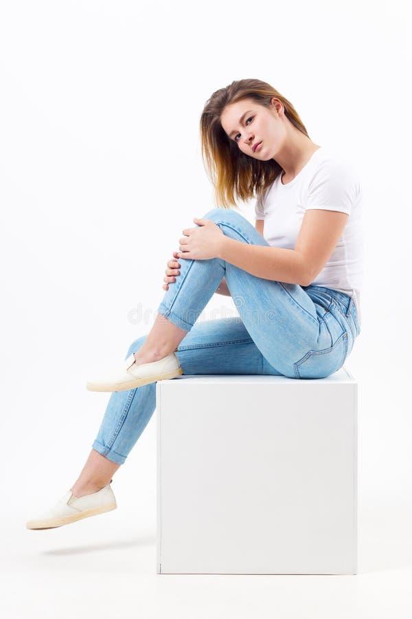 Flickatonåringen i jeans sitter på kuben i den vita studion arkivfoton