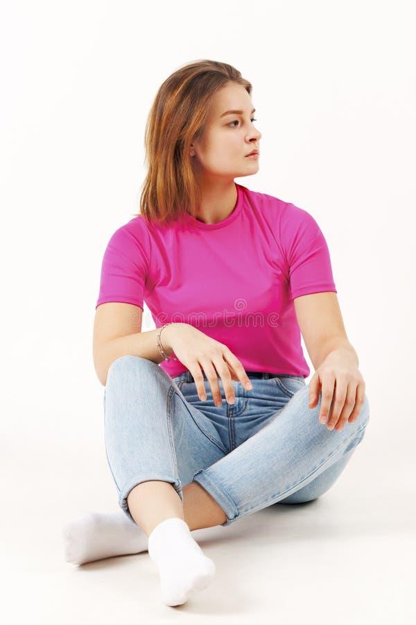 Flickatonåringen i rosa t-skjorta och jeans sitter på golv arkivfoton
