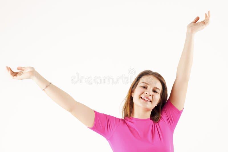 Flickatonåringen i rosa t-skjorta poserar med lyftta händer royaltyfri bild