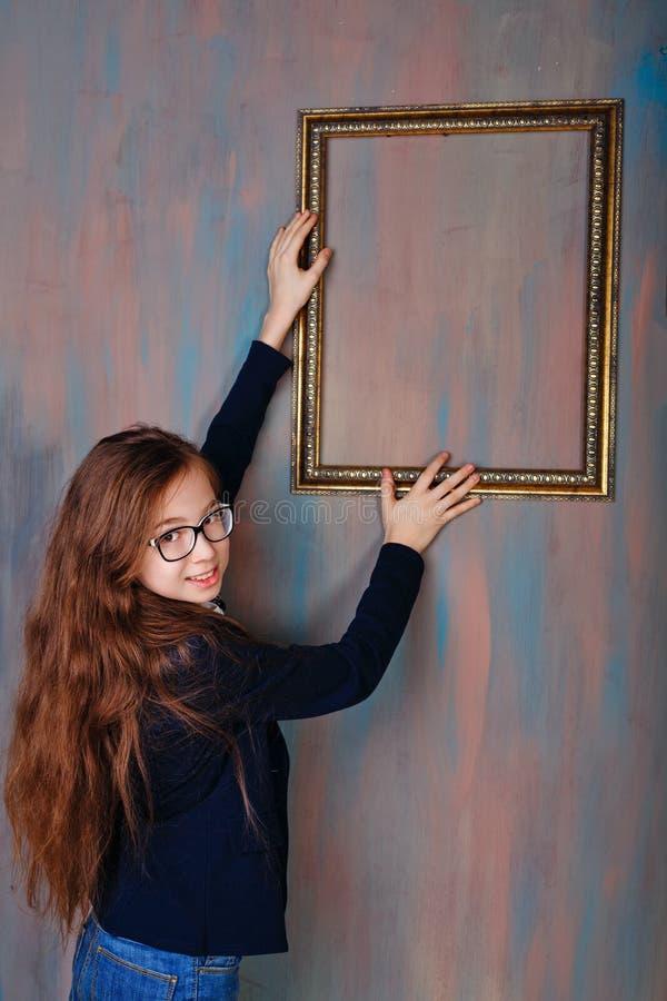 Flickatonåringen korrigerar en tom bildram arkivbild