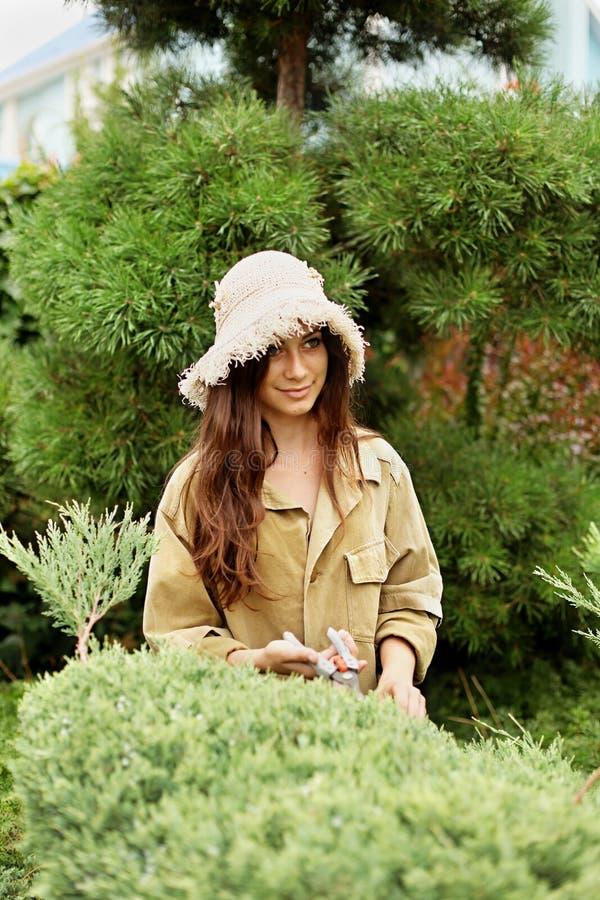 Flickaträdgårdsmästaren i snitt för funktionsduglig kläder och för sugrörhatt arbeta i trädgården vintergröna scissoors fotografering för bildbyråer