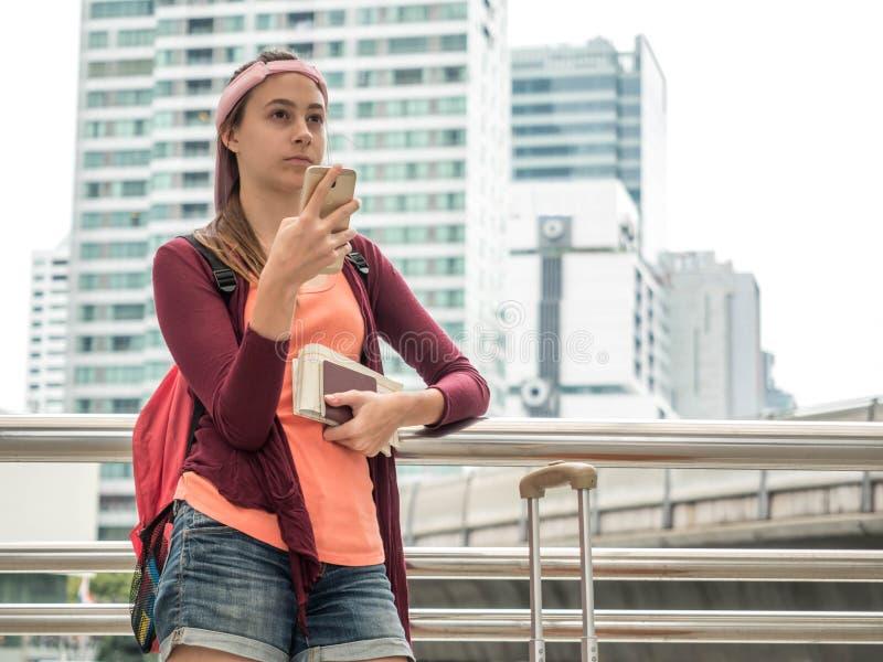 Flickaturister använder den smarta telefonen som står med bagage i stadsbakgrunden, ferietid arkivfoton