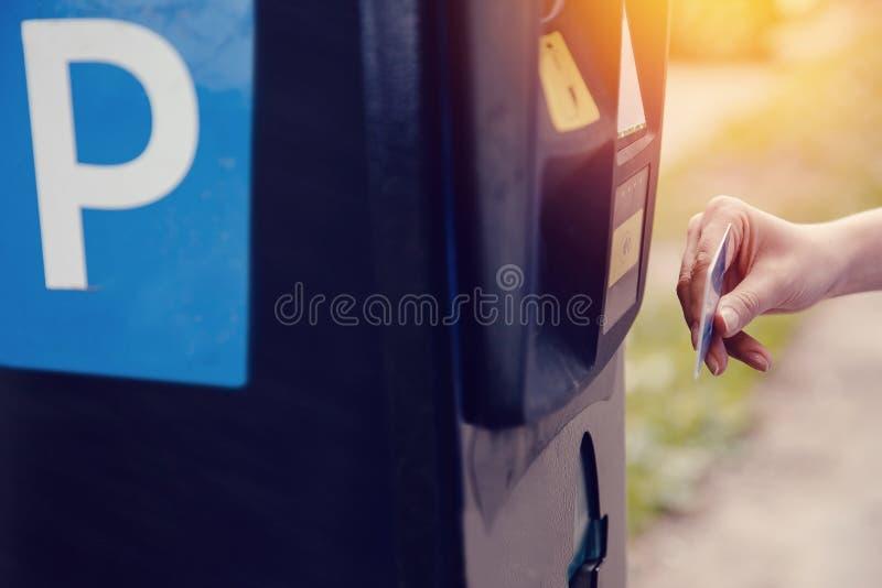 Flickatyper texten med hennes händer för framställning ut av biljetten för att parkera maskinparkering och betalning för lopp arkivfoto