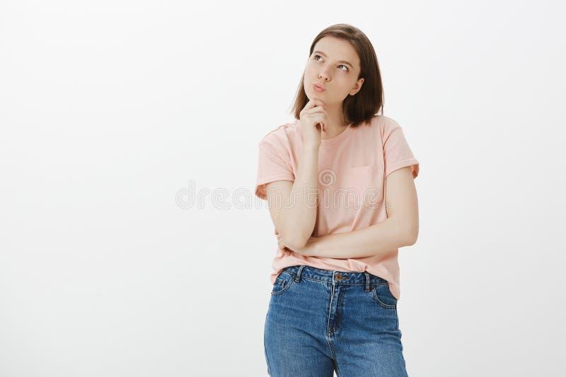 Flickaunder, om hon kan ha råd med en mer t-skjorta Den bestämda idérika och gulliga kvinnan som står i fundersamt, poserar royaltyfria foton