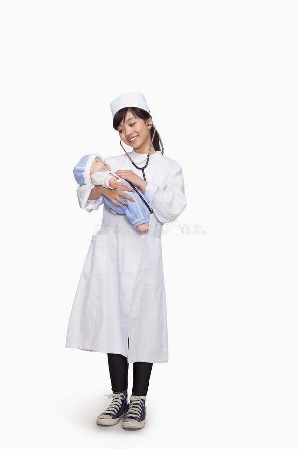 Flickauppklädd som doktorn som kontrollerar dockas livsviktiga tecken arkivfoton