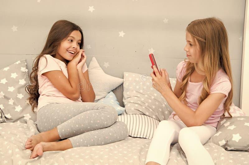 Flickav?nner som tar fotoet f?r sociala n?tverk Online-str?mvlogkanal Systrar i pyjamas kopplar av sovrummet och tar royaltyfria bilder