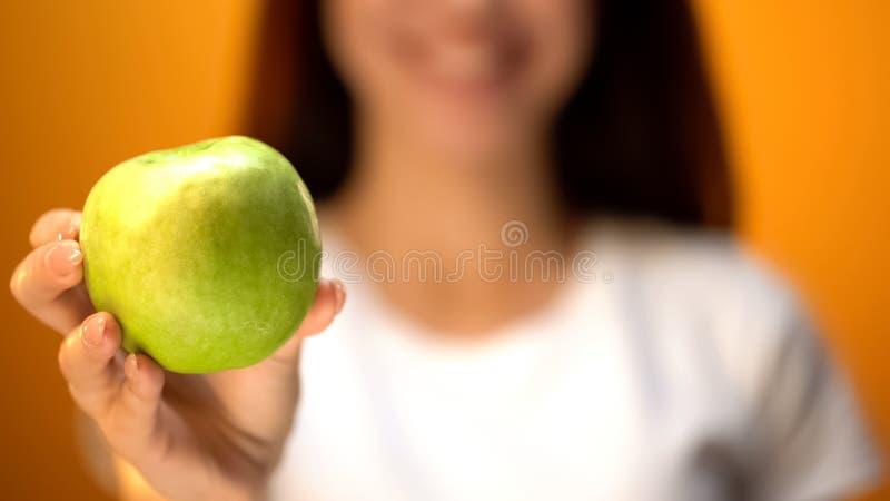 Flickavisningäpplet till kameracloseupen, hälsa och tandvård, vitaminer på bantar royaltyfria foton