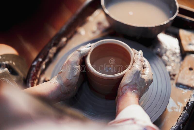 Flickhandskar som skulpterar Crockery på lerhjul Kreativa begåvade personer som skapar handgjorda presentationer arkivfoto