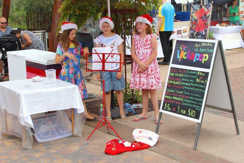 Flickor är sjungande julsånger i Alice Springs, Australien arkivbild