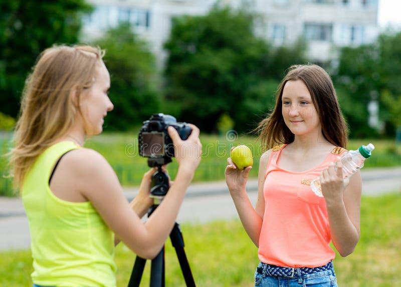 2 flickor är tonåringar I sommaren i parkera i natur Skriver videoen till kameran Här ` s hur man rymmer ett äpple royaltyfria bilder
