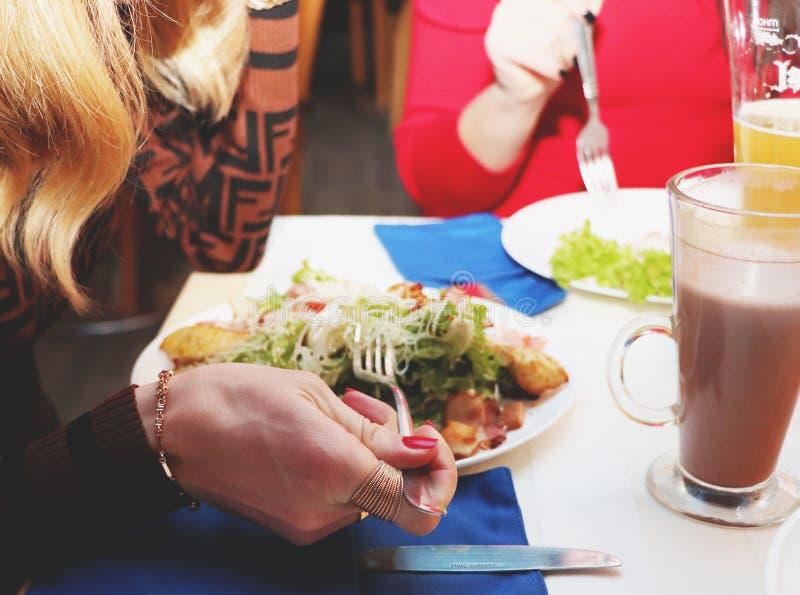 Flickor äter Caesar sallad i restaurangen arkivfoto