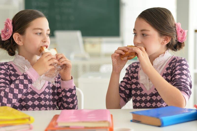 Flickor äter smörgåsar royaltyfria bilder
