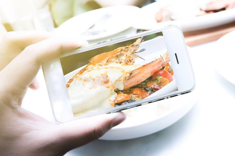 Flickor använder smartphones, tar bilder av mat i restauranger arkivfoto