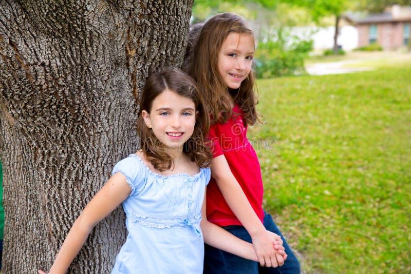 Flickor för barngruppvän som spelar på träd royaltyfria bilder