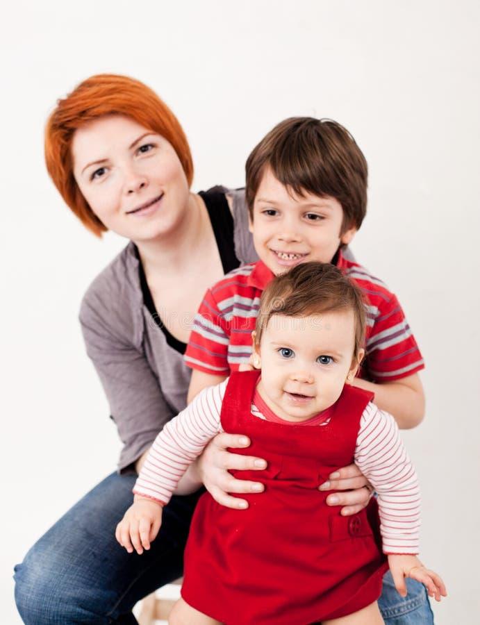 3 flickor för kamerasoffafamilj se sitting för orange stående för moder deras beträffande där fotografering för bildbyråer
