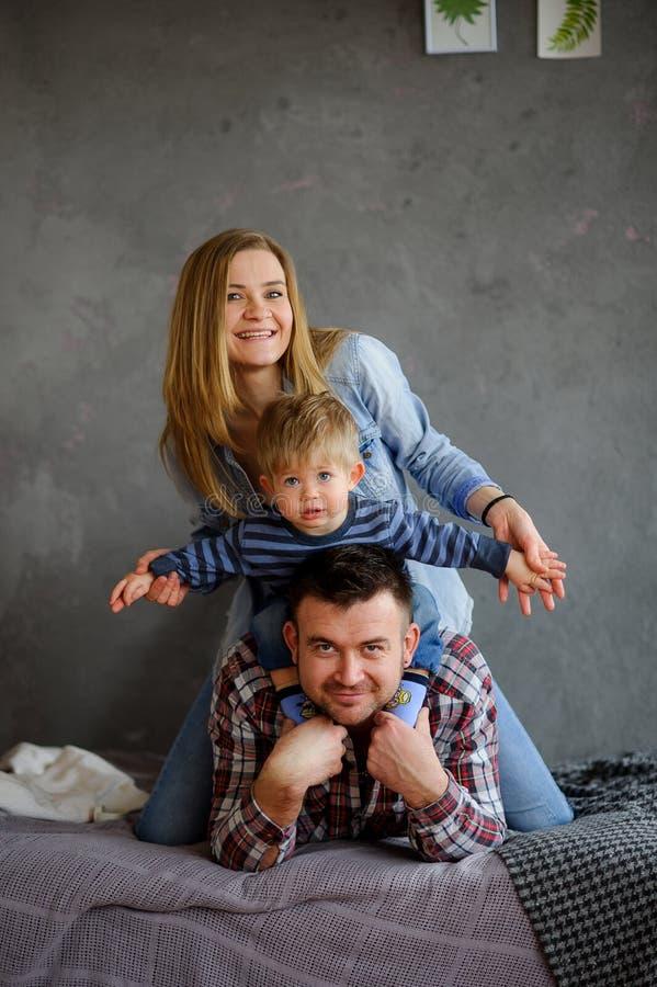 3 flickor för kamerasoffafamilj se sitting för orange stående för moder deras beträffande där Ung familj av tre personer royaltyfri bild
