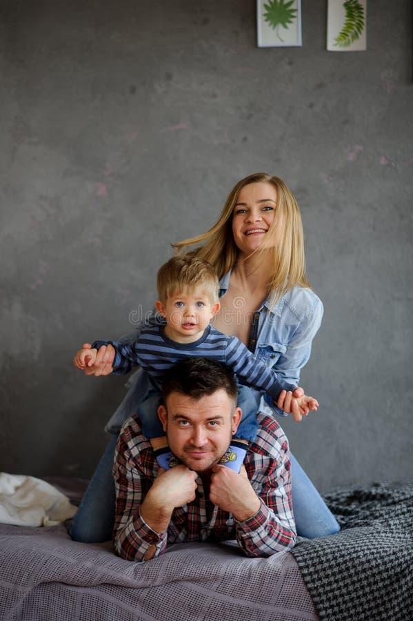 3 flickor för kamerasoffafamilj se sitting för orange stående för moder deras beträffande där Ung familj av tre personer arkivfoto