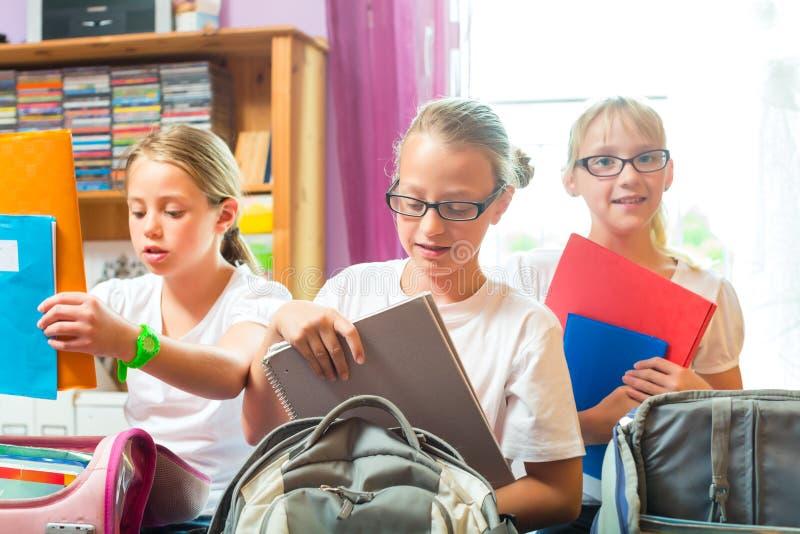Flickor förbereder påsar för skola med böcker