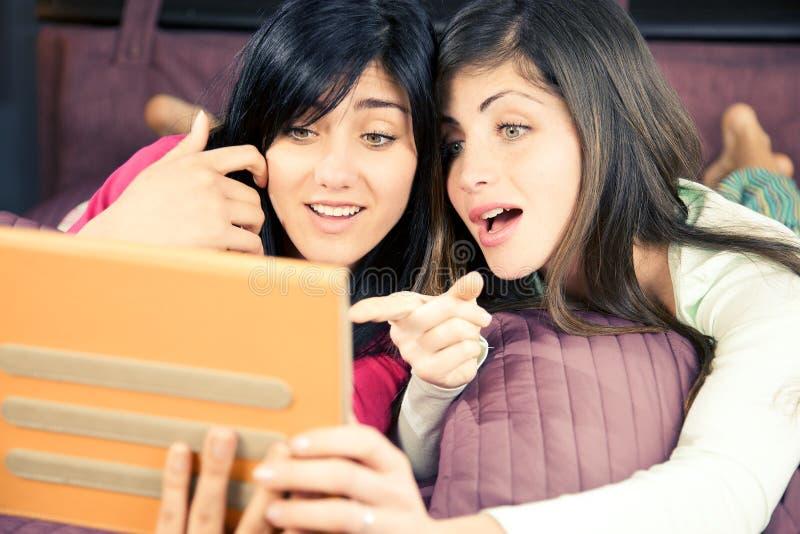 Flickor förvånat läs- socialt nätverk på minnestavlan arkivfoto