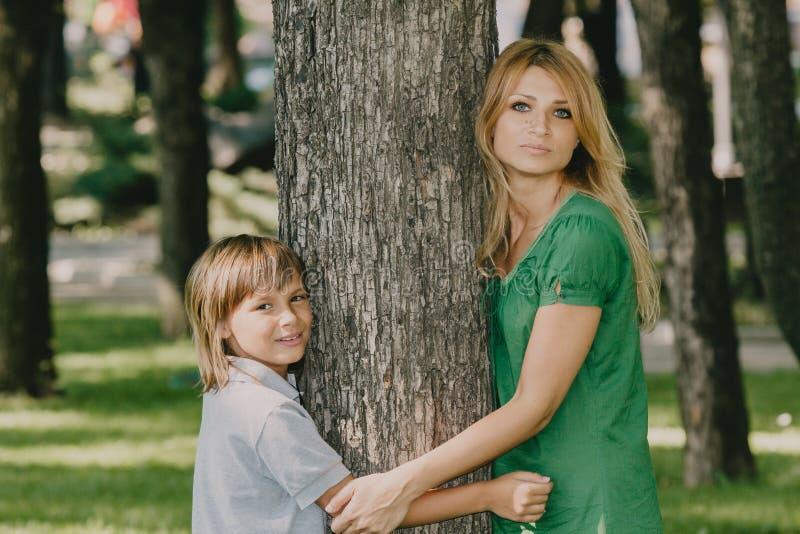 3 flickor f?r kamerasoffafamilj se sitting f?r orange st?ende f?r moder deras betr?ffande d?r Mamma och son bredvid stort träd arkivfoto