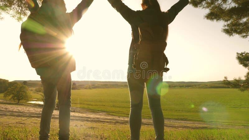 flickor f?r lagarbetsfotvandrare som lyfter upp hennes h?nder och att fira Victory And Enjoying Scenery teamworkmoder och dotter  royaltyfri foto
