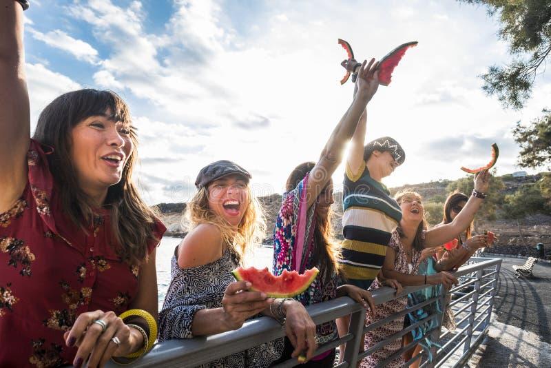 Flickor går galna i sommartid med vattenmelon utomhus- fritidbegrepp för kamratskap och för förhållande handelsresande och stag t royaltyfri bild