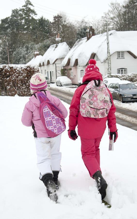 Flickor går till och med snö täckt by arkivbild