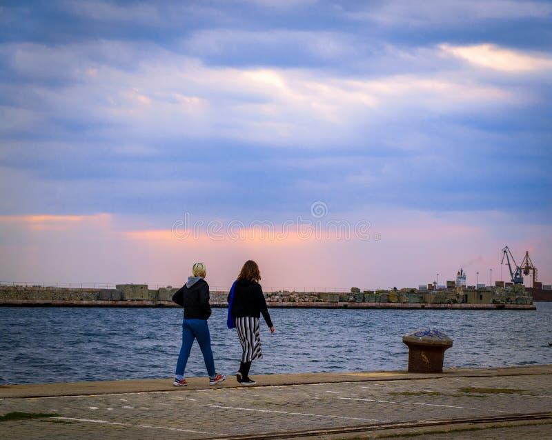 Flickor går vid vägen vid havet som de tycker om det bra vädret och solnedgången arkivfoton