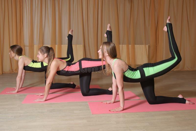Flickor gör övningar lyfter upp deras ben royaltyfri bild