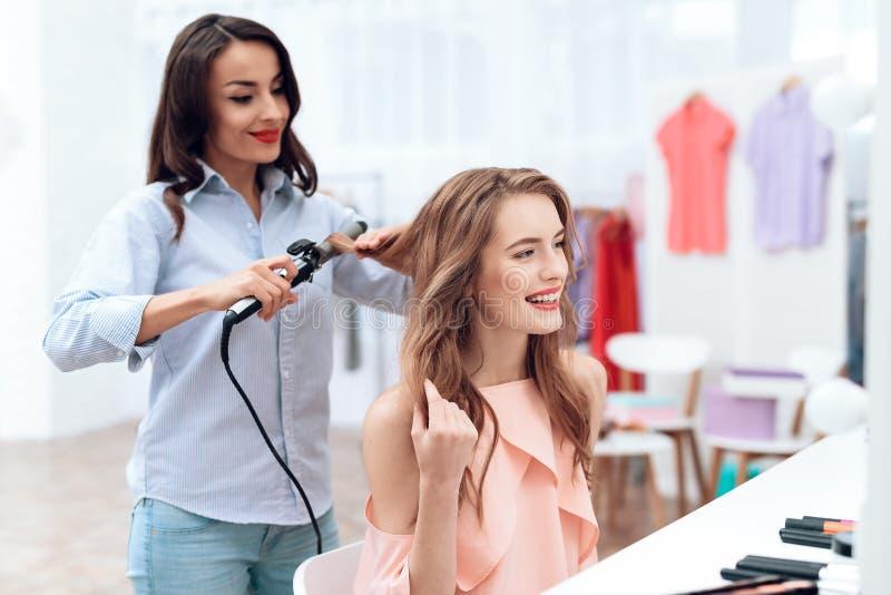 Flickor gör hår som utformar i visningslokalen Flickor gör hår som utformar i visningslokalen royaltyfri fotografi