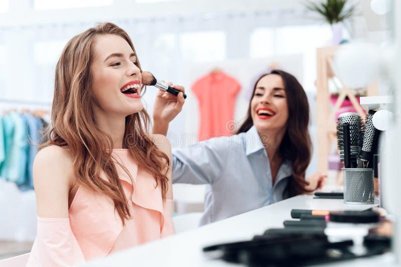 Flickor gör makeup i visningslokalen Två härliga flickor har gyckel och ler fotografering för bildbyråer