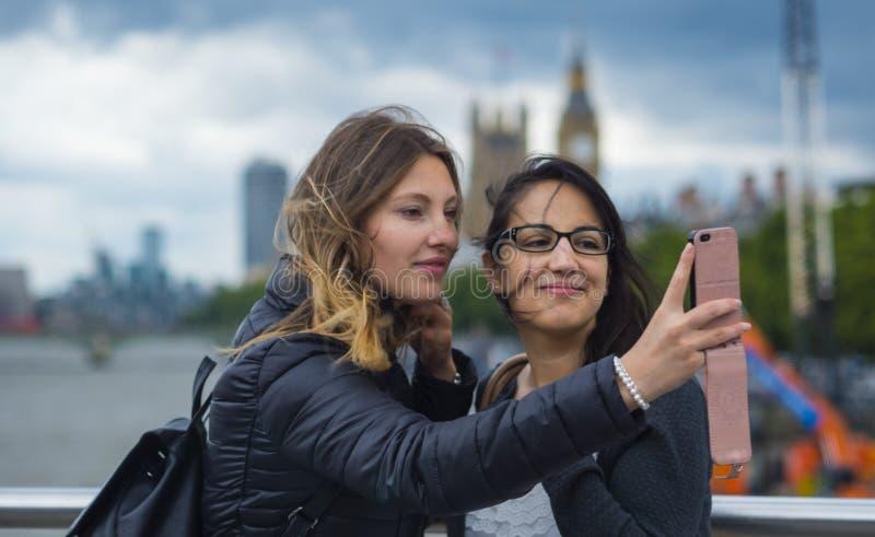 Flickor gör selfies under en stad att snubbla till London fotografering för bildbyråer